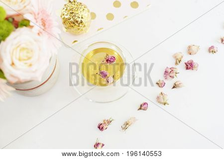 A Cup Of Healthy Herbal Tea With Dried Roses. Beautiful Fresh Flowers, Golden Pineapple, Notebook On