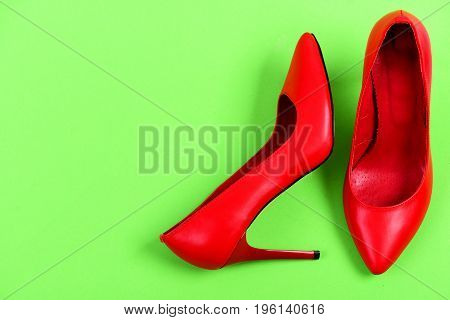 Red High Heel Shoes Isolated On Green Background, Top View