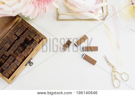 Handmade, Craft Concept. Wooden Rubber Stamps, Golden Scissors, Ribbons. Feminine Workplace Concept.