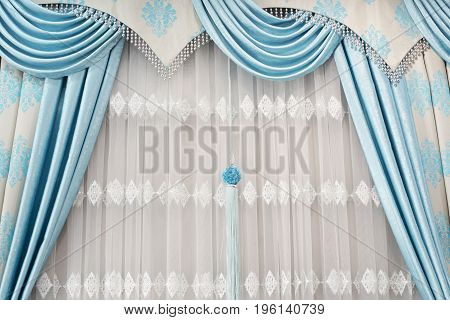 Part of beautifully draped curtain on the window in the room. Close up of curtain drapery with pendants. Luxury curtain home decor. Turquoise and blue panels. Lace drapery
