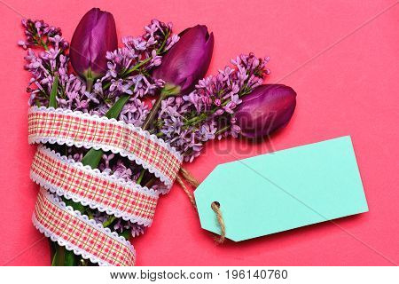 Cyan price tag tied to bunch of lilac flowers and tulips with red and white plaid ribbon isolated on salmon pink background top view and copy space. Spring gift and flower delivery concept