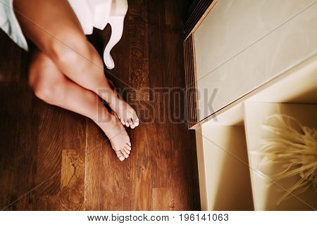 The beautiful bride in a white robe is sitting on a chair. Slim and nude legs of a young lady. Morning preparation before the wedding. View from above, horizontal image