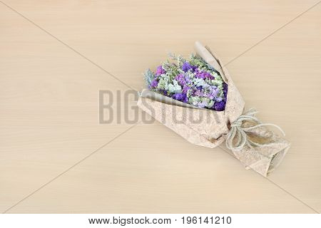 Statice flower bouquet on wooden background. free space for design