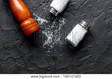 salt in bottle and saltcellar on black stone kitchen table background, top view mock-up