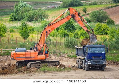 An excavator loading ground into the truck