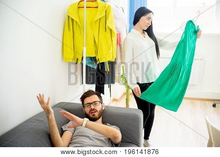 Bored husband waiting for wife while she decides what to wear