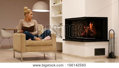 Young beautiful woman sitting in front of fireplace at home on a cold autumn day and reading book