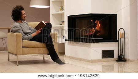 Young man sitting in front of fireplace at home on a cold autumn day and reading book