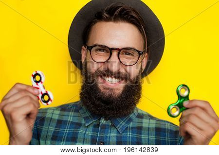 Smiling bearded young man with two spinners over yellow background