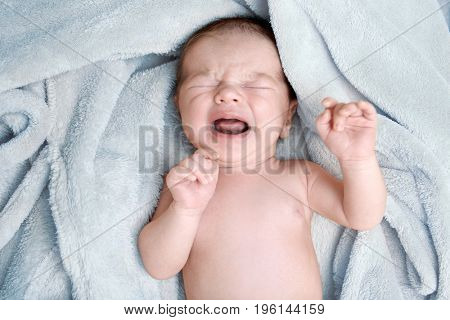 Crying newborn baby boy lying on soft plaid at home
