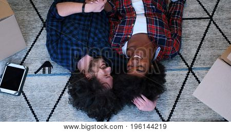 Top view of attractive young multiethnic couple moving in, holding hands, looking at camera and smiling while lying among cardboard boxes