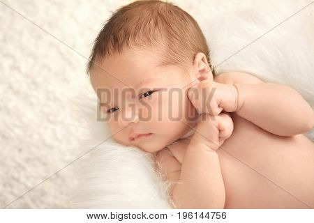 Newborn baby boy lying on soft plaid at home