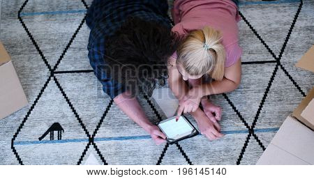 Top view of attractive young couple moving in, holding hands, while lying among cardboard boxes