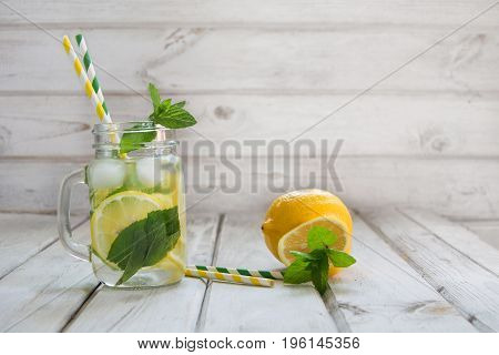 Summer drink water detox with lemon ice and mint in mason jar on a white wooden background.