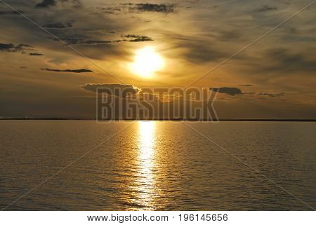 Sunset on the sea in the water reflect the rays of the setting sun