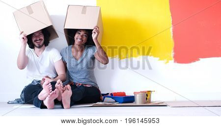 Happy young multiethnic couple relaxing and playing with cardboard boxes after painting a room in their new house on the floor