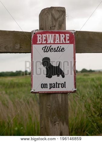 a beware dog patrol sign on wooden fence; Essex; UK
