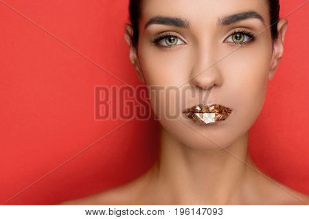 Attractive Fashionable Woman With Golden Sparkles On Lips, Isolated On Red