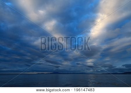 Scenic sky background, beautiful luminous clouds of V-shape on sunset in twilight, dramatic