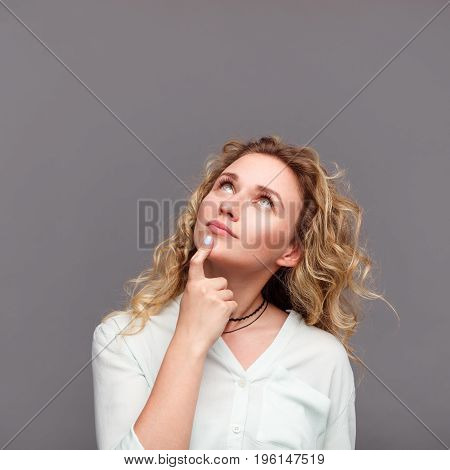 Cute blonde wavy haired woman touching chin wearing white blouse with rolled sleeves looking up.