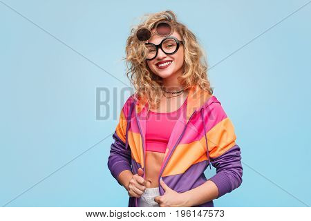 Young curly woman in sportive colorful clothing wearing creative sunglasses smiling at camera on blue.