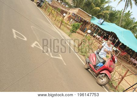 Goa India - March 02 2015: Pretty girl on the red bike shows to the inscription Paradise