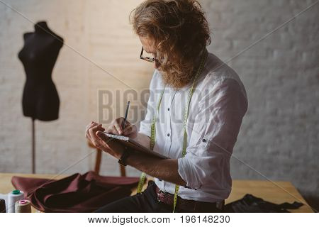 Bearded long haired man in glasses holding notebook writing with pen sitting on table.