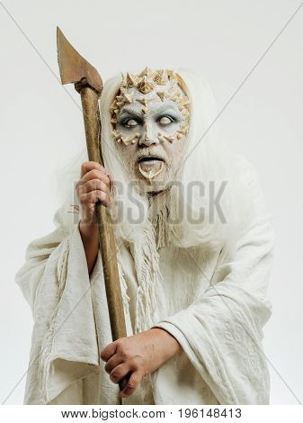 Wizard with long silver hair. Man with blind eyes. Demon with axe in hands on white background. Monster with thorns and beard on face. Horror and death concept.