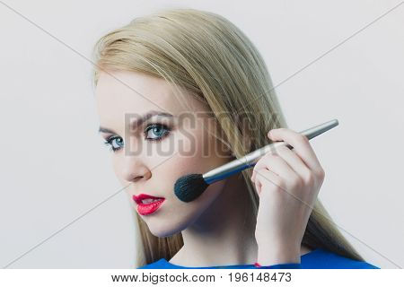 Woman Applying Makeup On Face Skin With Powder Brush
