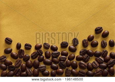 Roasted coffee beans on textured gold background, close-up, view from above