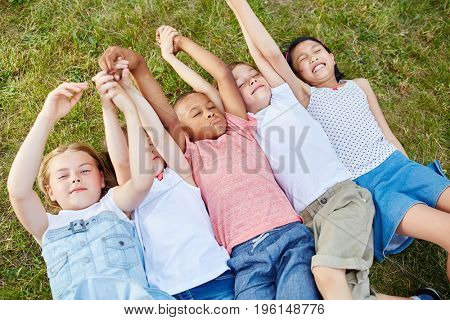 Interracial children on the grass together as group relaxing
