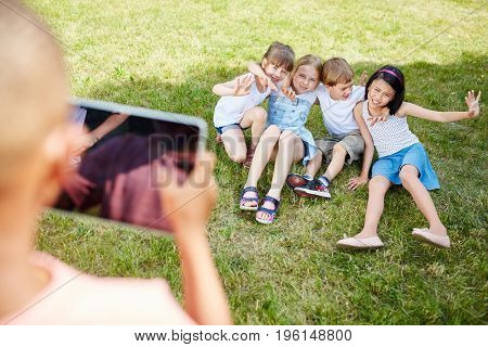 Boy takes photograph of children as friends with tablet for social media