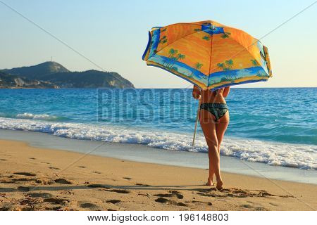 beautiful woman on tropical beach with umbrella