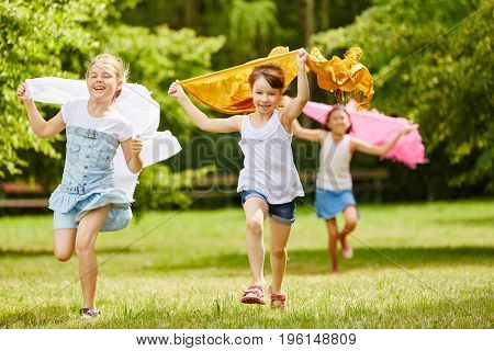 Children running in freedom in the park holding cloths in the air