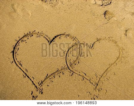 Two hearts drawn on sand of a beach. Valentines day on the beach. Top view Horizontal composition.