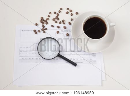 Coffee beans, magnifying glass and financial graph abstract close up for your ideas. Copy space. Financial graph top view.