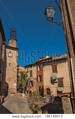 View of stone houses and tower in a street under blue sky, at the gorgeous medieval hamlet of Les Arcs-sur-Argens, near Draguignan. Located in the Provence region, Var department, southeastern France
