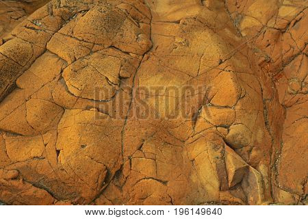 Texture of reddish cracked rock as background