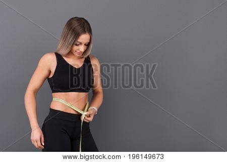 Female bodybuilder in sportswear measuring waist line with measuring tape on gray background.