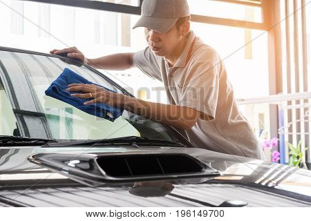 Auto service staff in grey uniform wipe the car glass with microfiber cloth-car detailing and valet concepts.