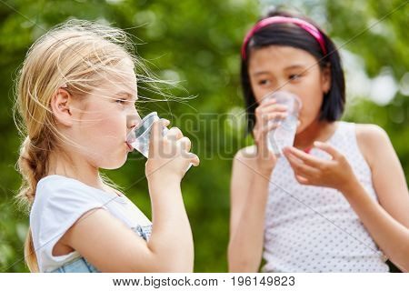 Two girls drink water as refreshment in summer