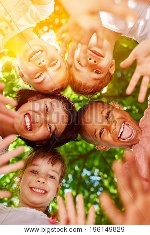 Interracial kindergarten group putting heads together in circle as motivation