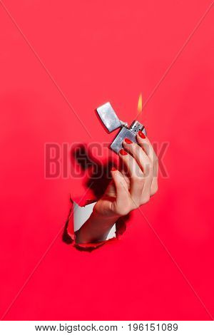 Vertical studio shot of hand through hole in red cardboard sheet holding flaming lighter.