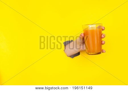 Crop anonymous female hand in hole of yellow paper holding glass of fresh juice.