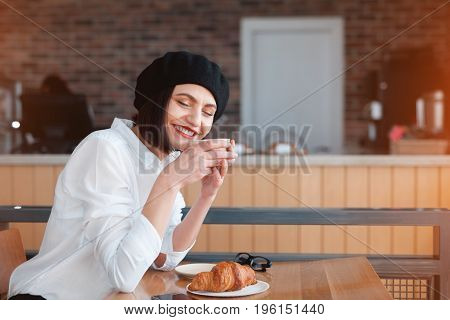 Charming adult woman in beret sitting in cafe with cup of coffee and croissant.
