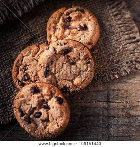 Chocolate cookies on dark napkin on wooden table. Closeup of a group of assorted cookies.