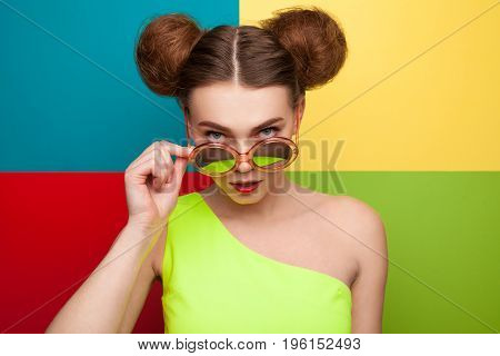 Redhead young woman with hairbuns wearing yellow dress touching sunglasses looking at camera.