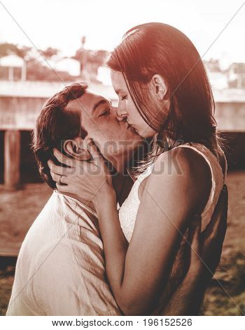 Man Holding His Wife And Giving Her A Kiss On A Warm Red Tone Photo