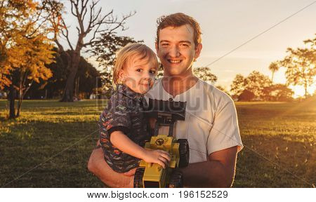 Father And Son Laughing Together At A Beautiful Sunset On A Park