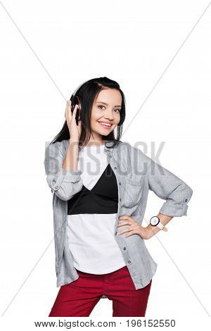 Attractive Girl Listening Music In Headphones While Standing With Hand On Waist And Smiling At Camer